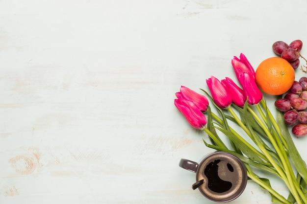 Arrangement von tulpen, früchten und kaffee