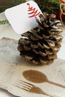 Arrangieren des tisches für das winterferienkonzept. tischdekoration im minimalistischen stil, der umriss auf holz von gabel und löffel, tannenzapfen mit tischkarte, rote serviette im hintergrund