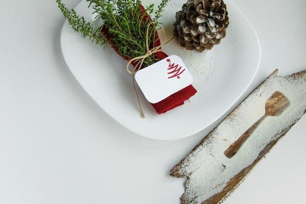 Arrangieren des tisches für das winterferienkonzept. tischdekoration im minimalistischen stil, rote serviette mit kräutern, umriss eines dessertlöffels, tannenzapfen und urlaubskarte