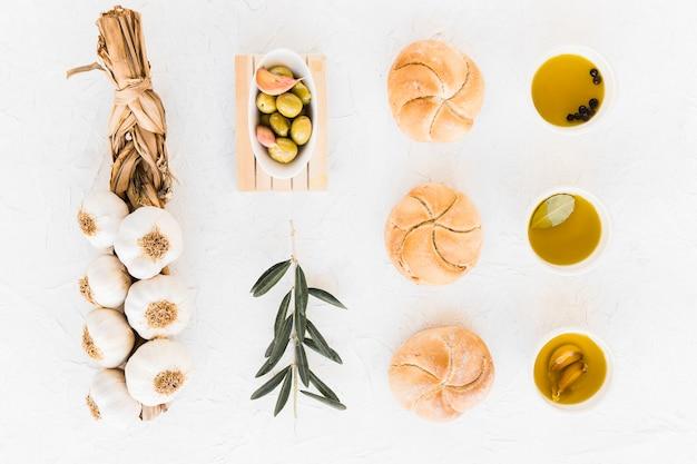 Arrangiert brötchen und öle mit oliven und zopf von knoblauchzwiebeln