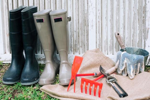 Arrangierte stiefel mit instrumenten im garten