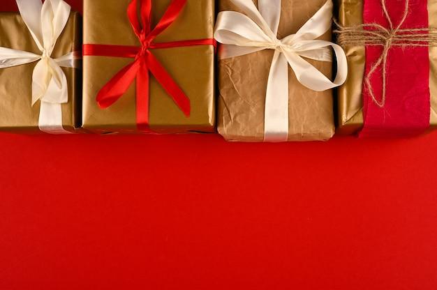 Arrangierte weihnachtsgeschenkboxen auf roter oberfläche.