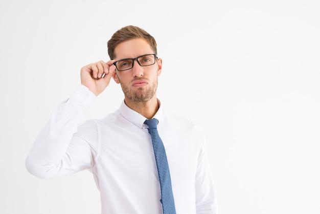 Arroganter geschäftsmann, der gläser justiert und kamera betrachtet