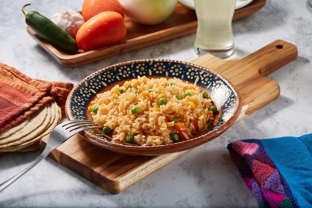 Arroz a la jardinera rojo con zanahoria chicharos y elote servido en plato mexicano