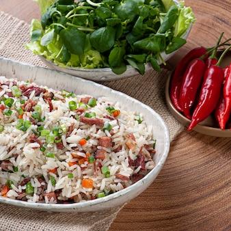 Arroz de carreteiro. typisches essen aus südbrasilien, hergestellt aus reis, getrocknetem fleisch, peperoni-wurst, speck und karotten.