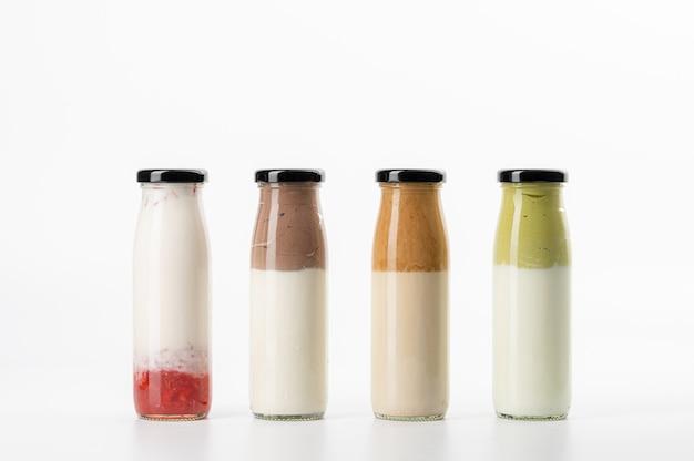 Art der milch, schokoladenmilch, grüntee-milch, kaffeemilch und erdbeermilch auf weiß isoliert