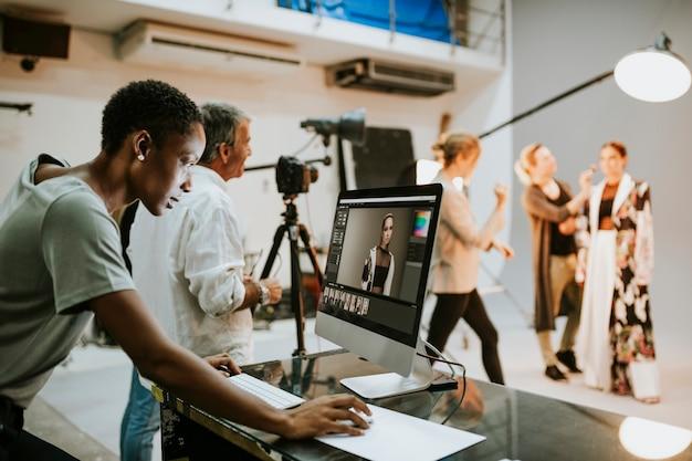 Art director, der fotos auf einem monitor überprüft