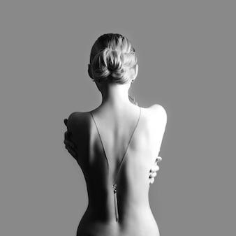 Art nude-mode aktrücken von blondinen auf grauer wand. frau umarmt sich mit den händen