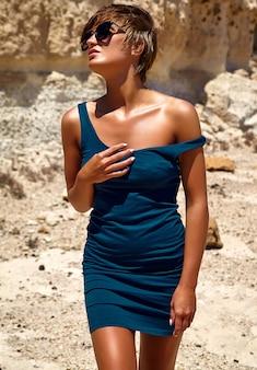 Art und weisestilvolles schönes junges brunettefrauenbaumuster im blauen kleid des sommers, das nahe sandfelsen aufwirft