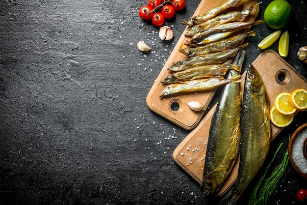 Arten von geräuchertem fisch mit scheiben von limette, zitrone, tomaten und kräutern auf schwarzem rustikalem tisch.