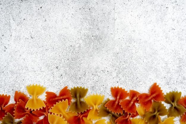 Arten von ungekochten nudeln. gelbe, grüne und rote farfalle-nudeln ungekocht auf hellem betongrund. . flache lage, draufsicht, copyspace