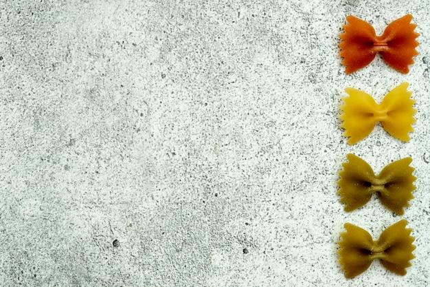 Arten von ungekochten nudeln. grünes, gelbes und rotes teigwaren farfalle trocken auf einem hellen konkreten hintergrund. . flache lage, draufsicht, copyspace