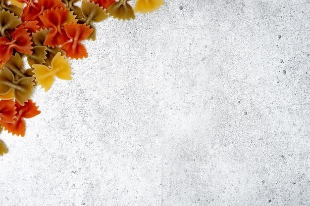 Arten von ungekochten nudeln. grünes, gelbes und rotes teigwaren farfalle trocken auf hellem konkretem hintergrund. flache lage, draufsicht, kopienraum