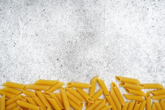 Arten von ungekochten nudeln. penne-teigwaren ungekocht auf einem hellen konkreten hintergrund. . flache lage, draufsicht, copyspace