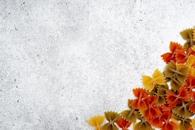 Arten von ungekochten teigwaren auf konkretem hintergrund