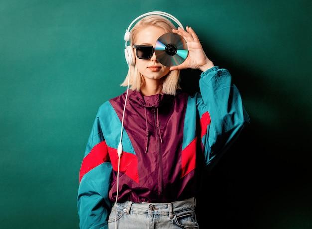 Artfrau in der punkkleidung der 90er jahre mit kopfhörern und cd