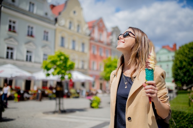 Artfrau in der sonnenbrille und in der eiscreme in gealtertem stadtzentrumquadrat.