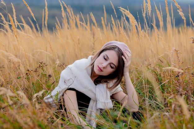Artfrau in der strickjacke sitzt im gelben gras an der landschaft mit bergen