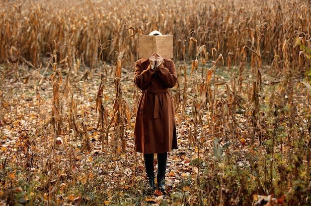 Artfrau mit buch auf maisfeld in der herbstzeitjahreszeit