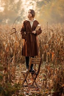 Artfrau mit buchaufenthalt auf stuhl auf maisfeld in der herbstzeitjahreszeit