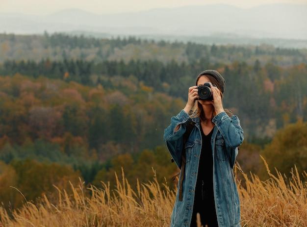 Artfrau mit fotokamera und rucksack an der landschaft mit bergen