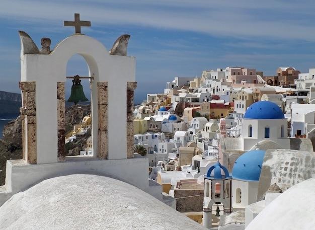 Artglockenturm der griechischen inseln und blaue hauben der kirche in oia-dorf, santorini-insel, griechenland