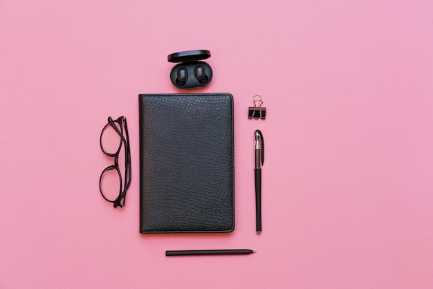 Artikel für geschäftsleute schwarze brille mit notizbuch und stift trendige drahtlose kopfhörer auf rosa hinter...