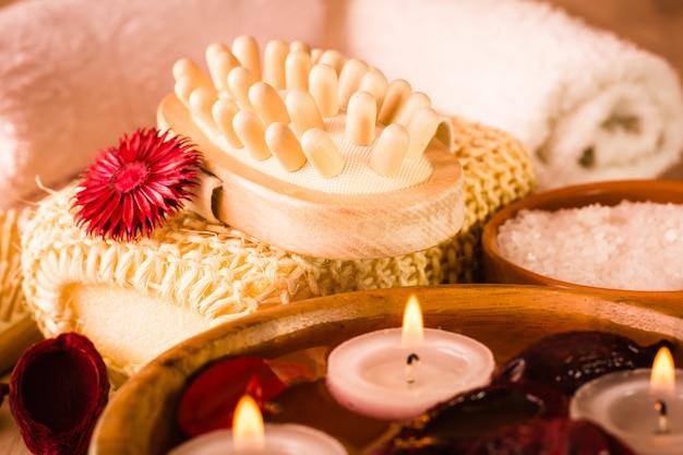 Artikel für spa-behandlungen. kerzen und duftende trockenblumen in wasser, meersalz, massagegerät und handtüchern