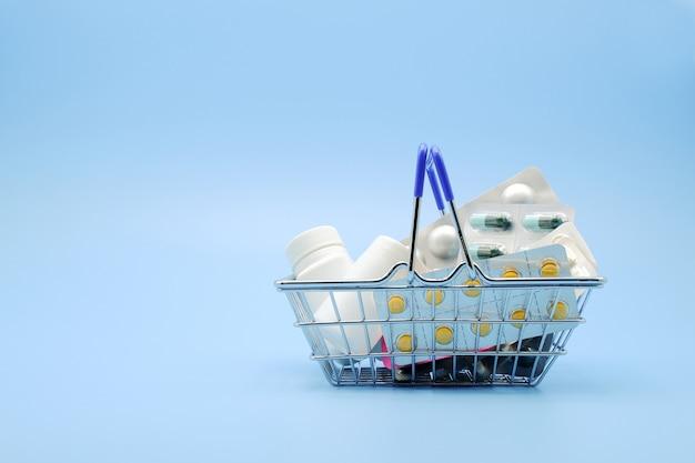 Arzneimittel im einkaufskorb mit drogenflasche lokalisiert auf blauer oberfläche