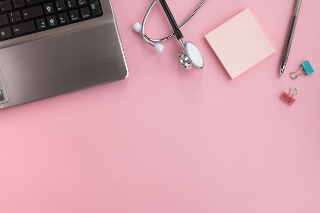 Arzt am arbeitsplatz. medizinisches stethoskop, laptop und stift auf rosa schreibtisch