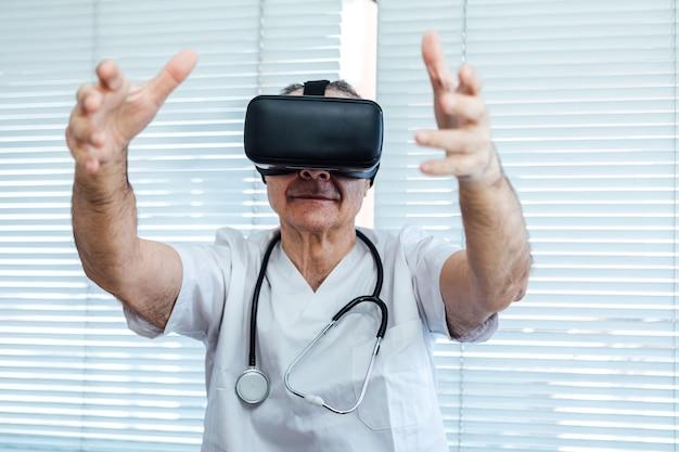 Arzt am fenster eines krankenhauses, der eine virtual-reality-brille für medizinische zwecke verwendet und etwas virtuelles mit seinen händen berührt