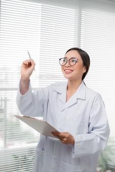 Arzt asiatische frau schreibt etwas mit marker