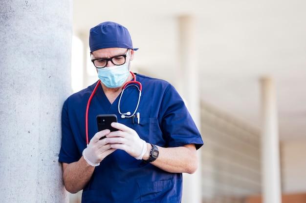 Arzt außerhalb des krankenhauses mit smartphone