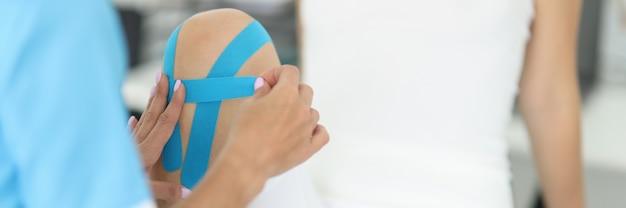 Arzt befestigt kinesio-tape am bein des patienten
