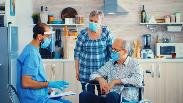 Arzt beim hausbesuch mit infrarot-thermometer bei behinderten senioren im rollstuhl, um die körpertemperatur zu überprüfen. behinderter älterer mensch bekommt empfehlung vom sozialarbeiter