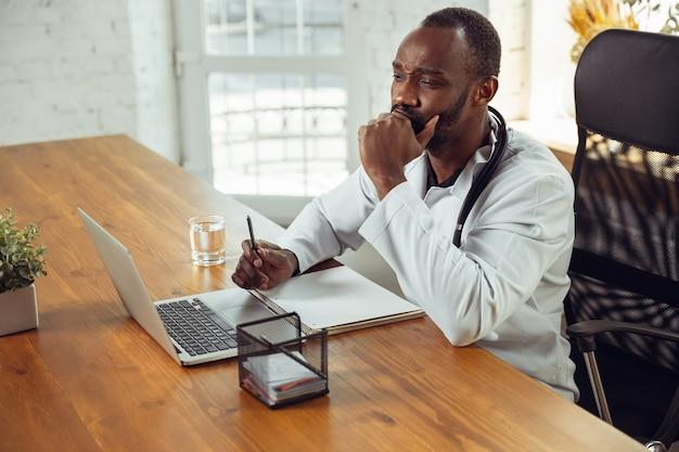 Arzt berät patienten, hört gestresster afroamerikanischer arzt während seiner arbeit mit patienten zu und erklärt rezepte für medikamente. tägliche harte arbeit für gesundheit und leben retten während der epidemie.