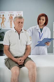 Arzt beruhigt älteren patienten, der nach einer schweren verletzung eine langfristige rehabilitation benötigt