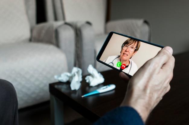 Arzt bespricht krankheit mit krankem mann durch videoanruf am telefon