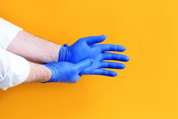 Arzt blaue schutzhandschuhe anziehen.