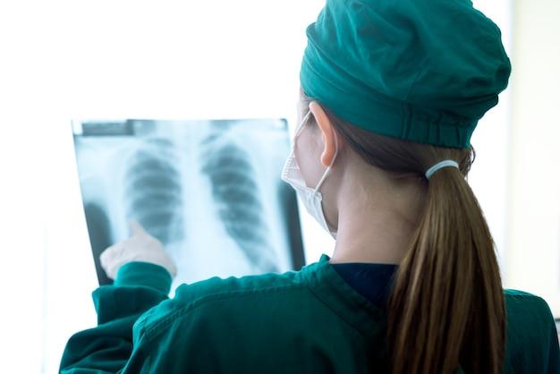 Arzt der ärztin, der röntgenstrahlen in einem krankenhaus betrachtet