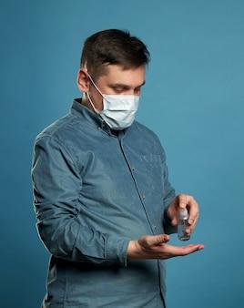 Arzt, der antibakterielles spray auf geduldige hände auf blauer wand anwendet