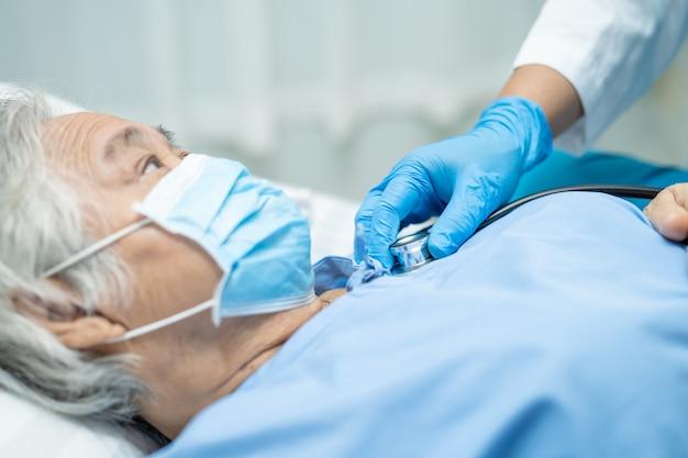Arzt, der asiatische ältere patientin auf schutz des covid-19-coronavirus überprüft.
