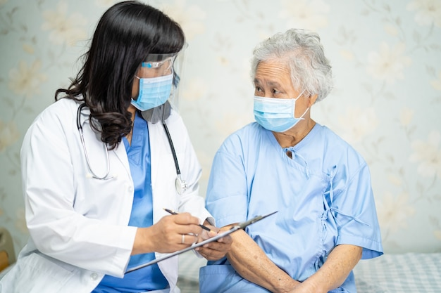 Arzt, der asiatische ältere patientin prüft, die eine gesichtsmaske im krankenhaus trägt.