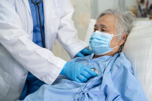 Arzt, der asiatische ältere patientin prüft, die eine gesichtsmaske trägt, um covid-19 coronavirus zu schützen.