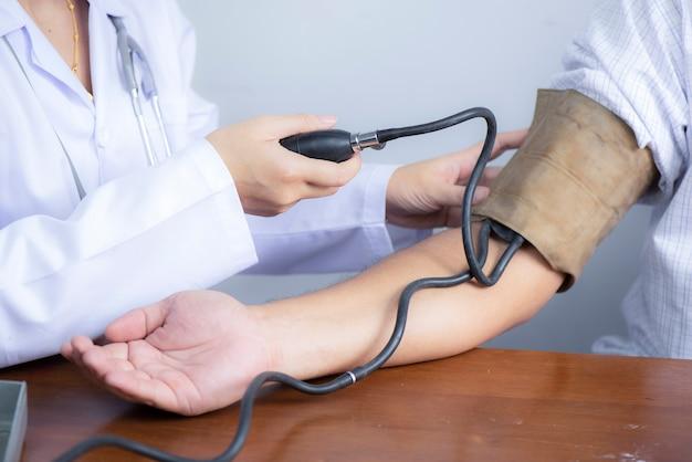 Arzt, der blutdruckmessgerät mit stethoskop verwendet, das blutdruck prüft