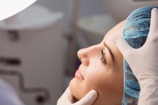 Arzt, der das gesicht der frau auf kosmetische behandlung untersucht