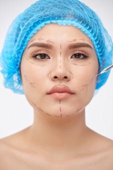 Arzt, der das gesicht einer ernsten jungen frau markiert und ein anästhetikum vor der plastischen operation injiziert