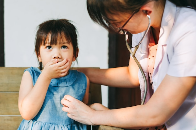 Arzt, der das stethoskop atemgeräusch des kindes überprüfend verwendet. krankheits- und gesundheitskonzept.