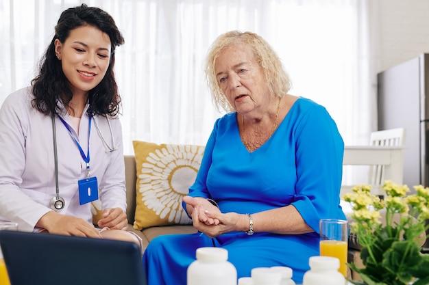 Arzt, der dem patienten informationen auf dem tablett zeigt