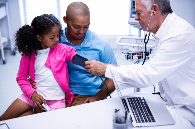 Arzt, der den blutdruck des patienten überprüft